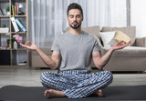 Portrait of calm bearded male sitting on yoga carpet in living room - 195957343