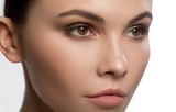 Close up of face of serious young woman looking forward with confidence. Beauty concept