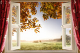 Open window with fresh air and countryside scenery views. Red curtains opened show a modern window in a house in a rural location