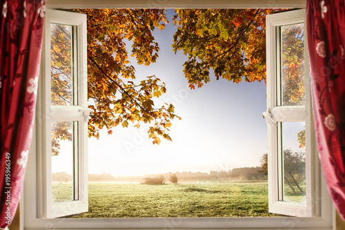 Fototapeta Open window with fresh air and countryside scenery views. Red curtains opened show a modern window in a house in a rural location