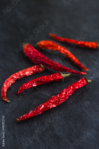 Deurstickers Hot chili peppers Dried pods of red chili peppers on a dark background close-up - Concept of spicy cuisine