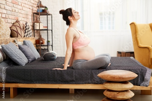 Plakat Pregnant woman exercising relaxing at home