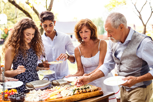 Family celebration or a garden party outside in the backyard. - 195973569