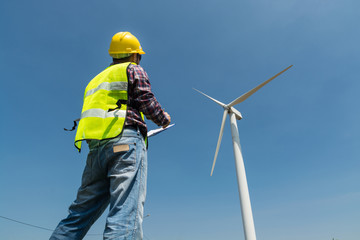 Electric Engineer writing report on Clipboard with Wind turbine power Generator