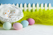 Easter eggs, white basket, feathers, green grass and white fence on blue background