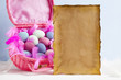 Blank paper sheet and pink basket full of colored eggs