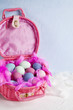 Happy Easter - pink basket full of colored eggs and feathers on blue and white background