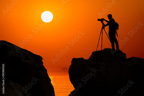 Poster Oranje eclat silhouette of photographer on top of mountain at sunset background
