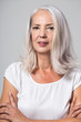 Attractive youthful fifty year old woman with shoulder length grey hair looking directly into the lens with a smile