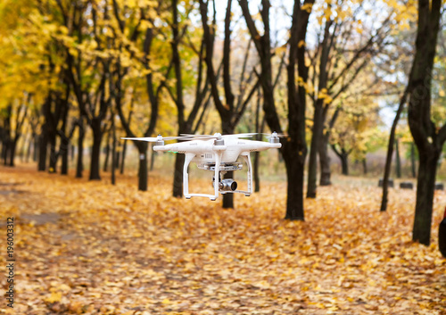 Fototapeta Dron with a video camera in the autumn park