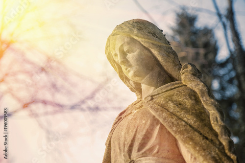 Virgin Mary statue. Vintage sculpture of sad woman (Religion, faith, suffering, love concept)