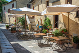 Cafe tables and chairs in a street in the village of Bagno Vignoni, Tuscany, Italy