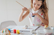 Close view of little girl painting easter eggs