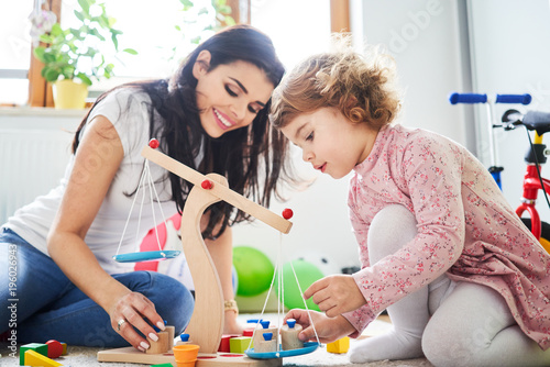 Mother spending time with her daughter playing with toys