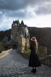 Young unrecognizable woman stands back on the road leading to a beautiful castle. Fabulous medieval place. Sunny rays fall on the hair of elegant female traveler. Trendy girl is traveling in Europe - 196027190