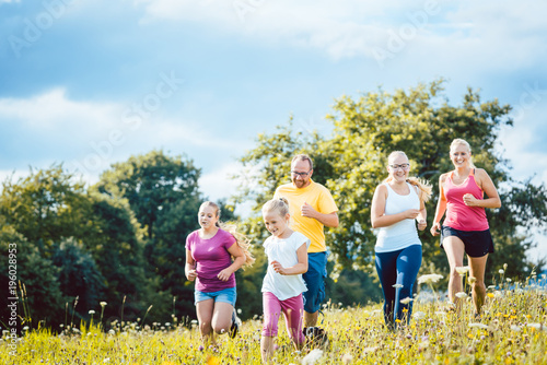 Family running on a meadow with flowers for sport - 196028953