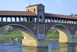 Italy - Pavia - The Covered Bridge (also called Ponte Vecchio) on the ticino with the Cathedral of the city in the background