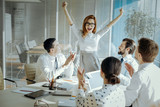 Exhilarating news. Upbeat young woman celebrating receiving good news during the meeting with her colleagues, raising her hands in triumph - 196042375