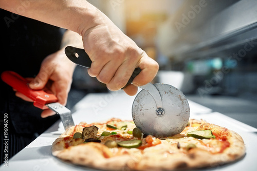 Keuken foto achterwand Pizzeria cook cutting pizza to pieces at pizzeria