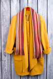 Flat lay yellow coat and scarf. Wooden desk surface background. - 196048563