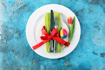 Festive table setting for Easter with fork, knife and tulip.