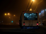 White trolleybus driving dangerously in the fog at night
