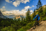 Tourist cycling in Cortina d'Ampezzo, stunning rocky mountains on the background. Man riding MTB enduro flow trail. South Tyrol province of Italy, Dolomites. - 196055769