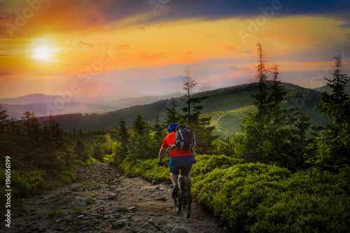 Halna rowerzysta jazda przy zmierzchem na rowerze w lato gór lasu krajobrazie. Man cycling track szlak MTB przepływu. Aktywność na świeżym powietrzu.
