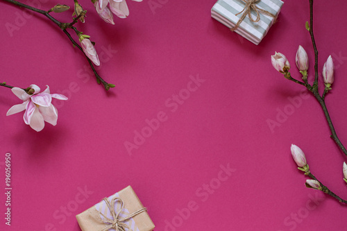 Fototapeta Magnolia flower branch on the purple background with gifts. Copy space