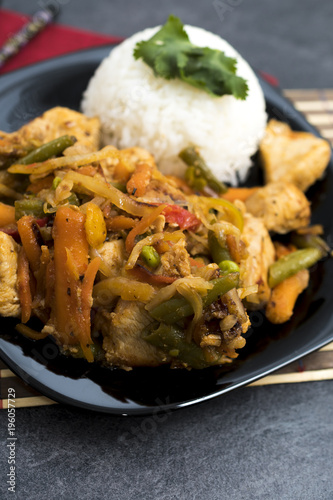 Fried vegetables with turkey meat and rice on the black plate. Asian delicates dishes with chili sauce.