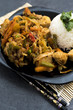 Fried vegetables with turkey meat and rice on the black plate. Asian delicates dishes with chili sauce. - 196057916