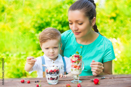 Foto op Canvas Sap Beautiful happy mother and her child boy eating layered dessert in green garden in sunny summer day