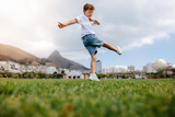 Boy playing football in a park - 196064181