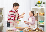 Mother and daughter cooking at home, making the dough for buns - 196071523