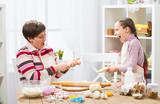Mother and daughter cooking at home, making the dough for buns - 196071552