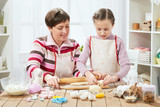 Mother and daughter cooking at home, making the dough for buns - 196071588