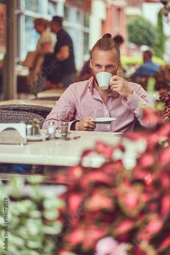 Foto op Canvas Kapsalon A handsome redhead male with a stylish haircut and beard in pink