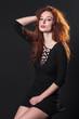 red-haired model posing in studio on dark background