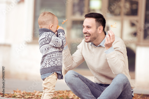Little boy and father playing with leaves - 196087917