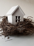 Buying, selling a house, a white house in a nest . Your house is an investment. - 196091190