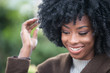 Happy African American woman fixing her hair