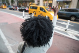 Woman with black curly hair hailing a taxi cab  - 196092564