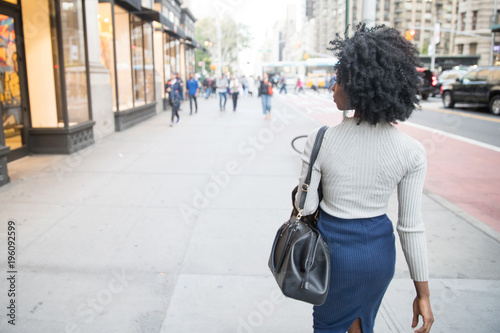 Poster Woman with black curly hair walking on a city sidewalk