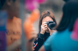 Woman photographer  holding dslr camera taking photos