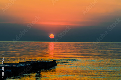 Deurstickers Oranje eclat orange red sun rises above the golden waves of the ocean
