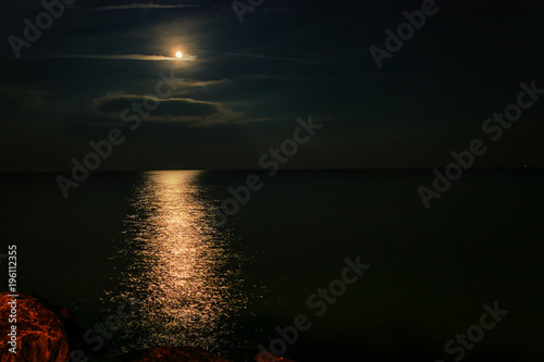 Aluminium Zwart A bright round moon in the clouds, in the night sky over the ocean and a moon track on the water