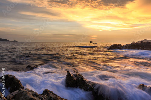 Fotobehang Strand Seascape of wave on rock , Long Exposure at Sunset on the beach in Phuket Thailand.