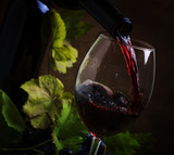 Red wine pouring into a glass, vintage wood background, selective focus - 196114157