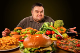 Diet fat man who makes choice between healthy and unhealthy food . Overweight male with hamburgers, french fries. Feast on the occasion of the feast. - 196128744