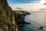 Scenic view of cliffs in Irish coast with green hills at sunset. - 196129586